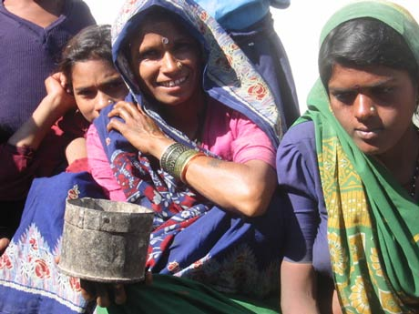 Dalit women in Uttar Pradesh with their local measuring container